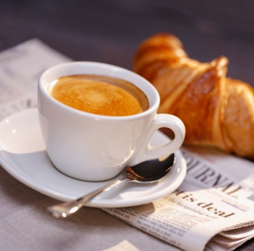 Catch up with the news: Coffee, croissant, glasses and newspaper