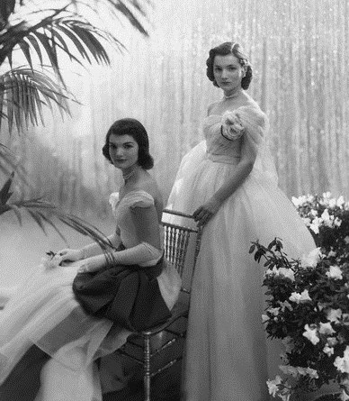 Jacqueline Bouvier (later Jacqueline Kennedy Onassis), seated with her sister Caroline Lee Bouvier, standing behind her, wearing ball gowns.