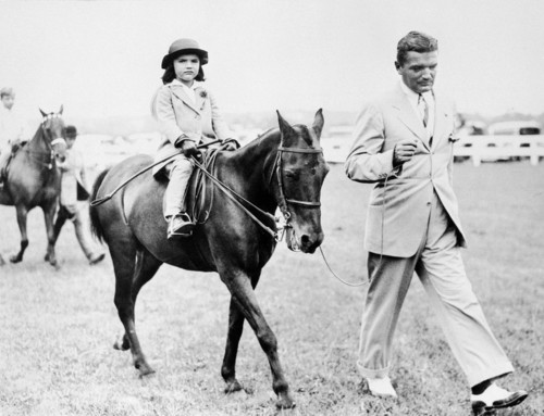 Photo taken 12 August 1934 in the American countryside of Jacqueline Kennedy Onassis as a child riding a pony led by her father John Vernou Bouvier III.